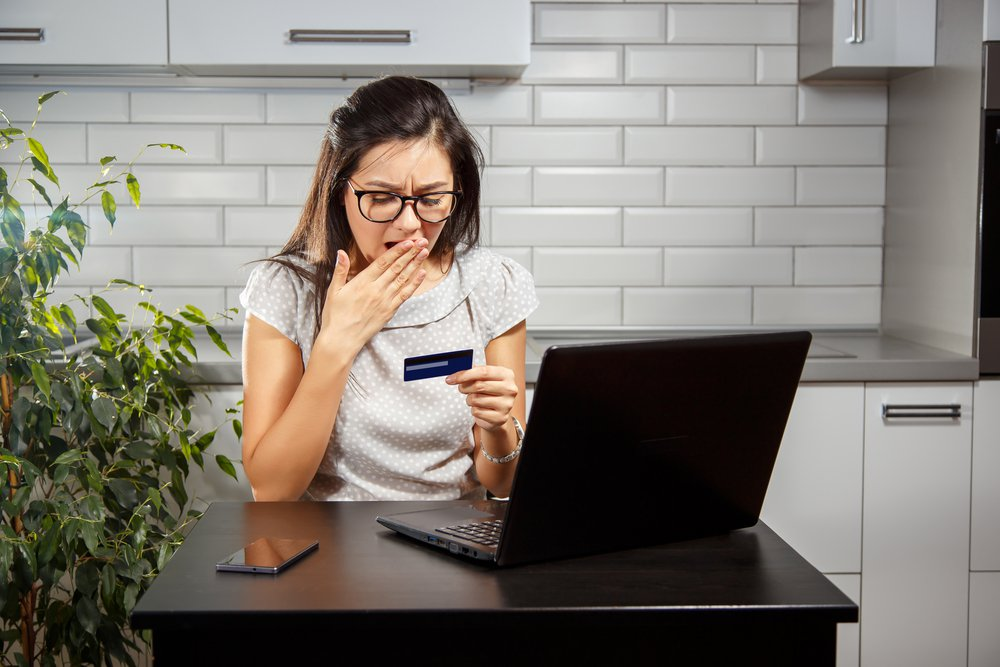 Schocked woman with the credit card near laptop