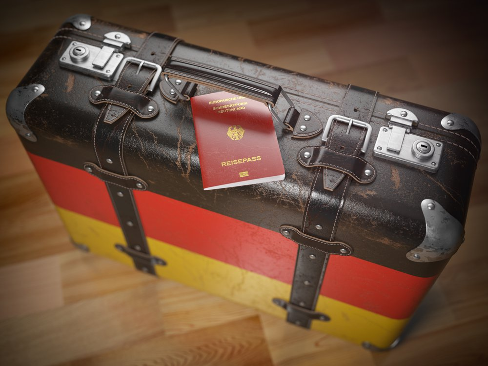 Passport of Germany and suitcase with flag of Germany