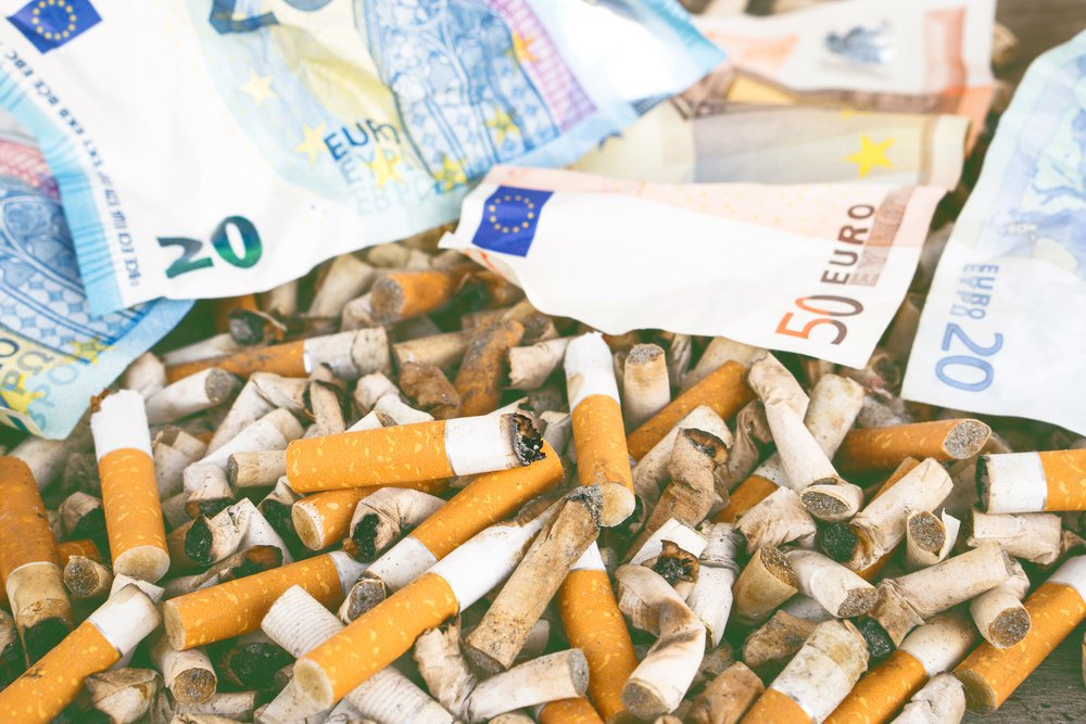 Cigarette butts with euro banknotes