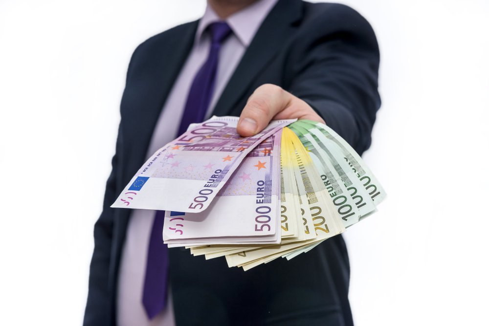 Man gives a pack of euro banknotes