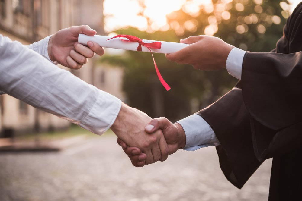 graduate in academic dress taking his diploma and shaking hand