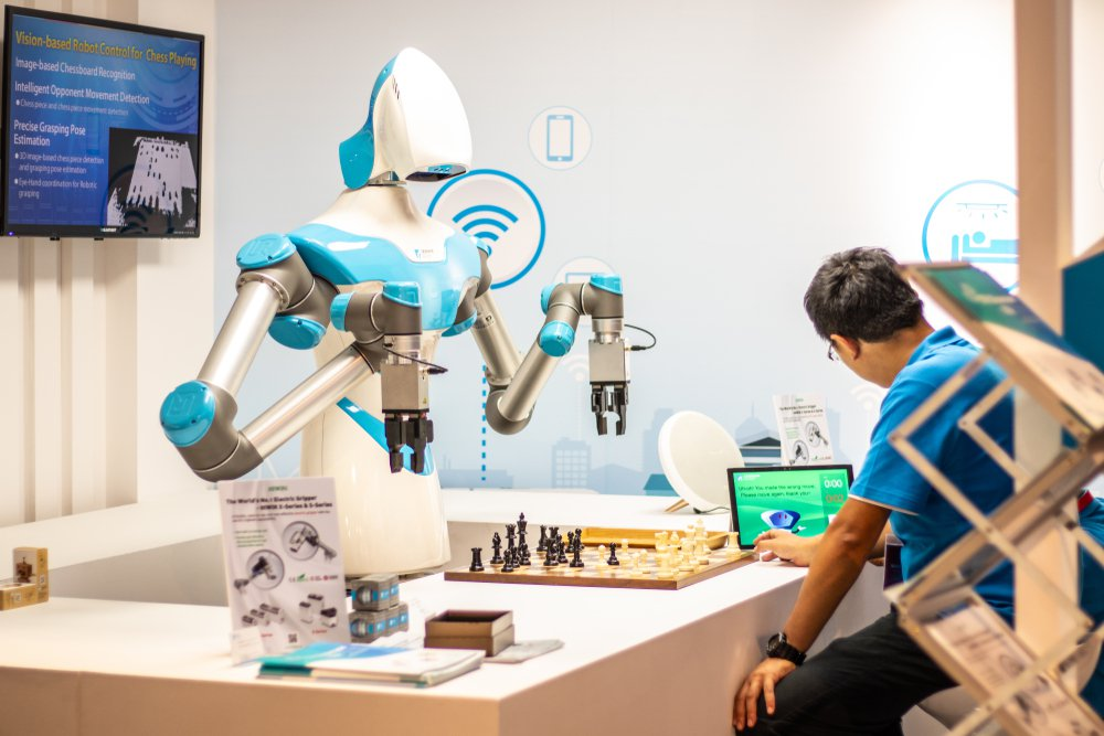 robot humanoid plays a match of chess with an IFA visitor