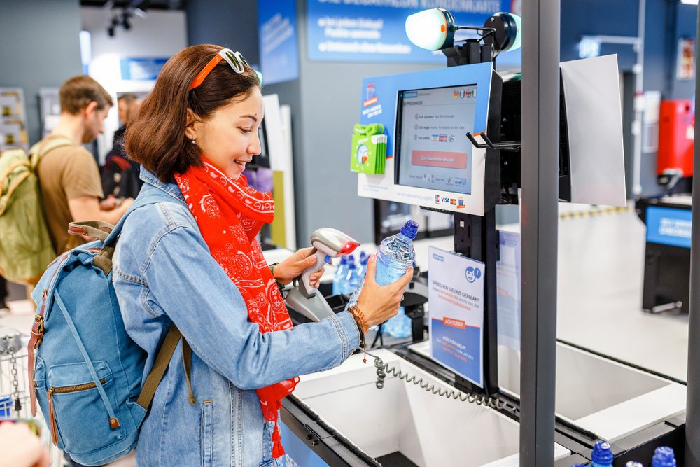 woman buying bottle of water at supermarket self-service cash register