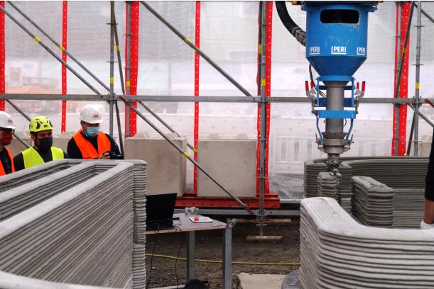 большой принтер выкладывает стены из бетона строители наблюдают фото
