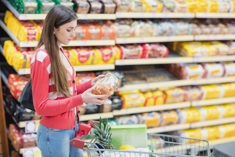 Девушка в супермаркете с тележкой фото