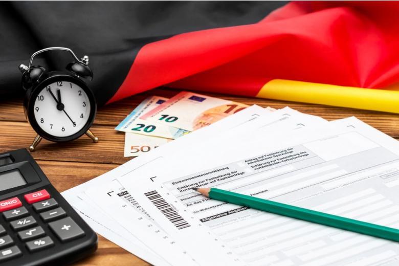 на столе лежит немецкий флаг, калькулятор и письмо