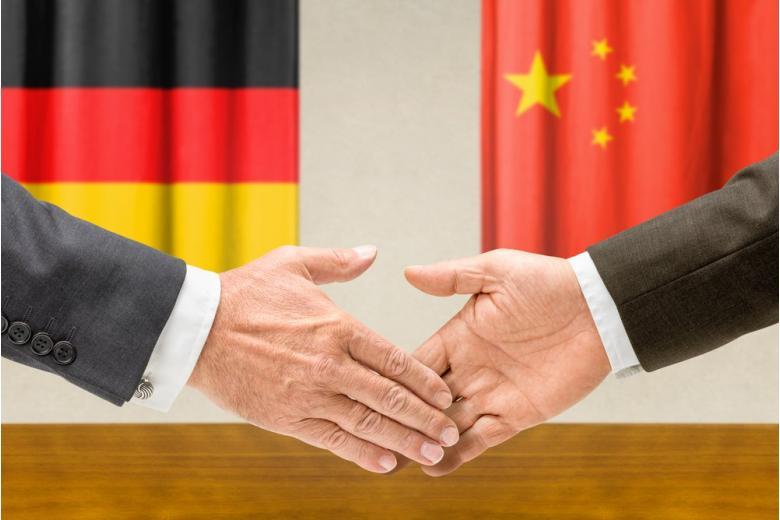 Рукопожатие на фоне флагов Германии и Китая