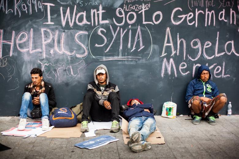 Мигранты сидят на земле