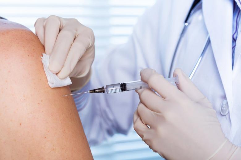 Врач вводит вакцину пациенту