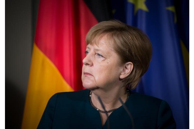 Ангела Меркель на фоне флагов Германии и ЕС