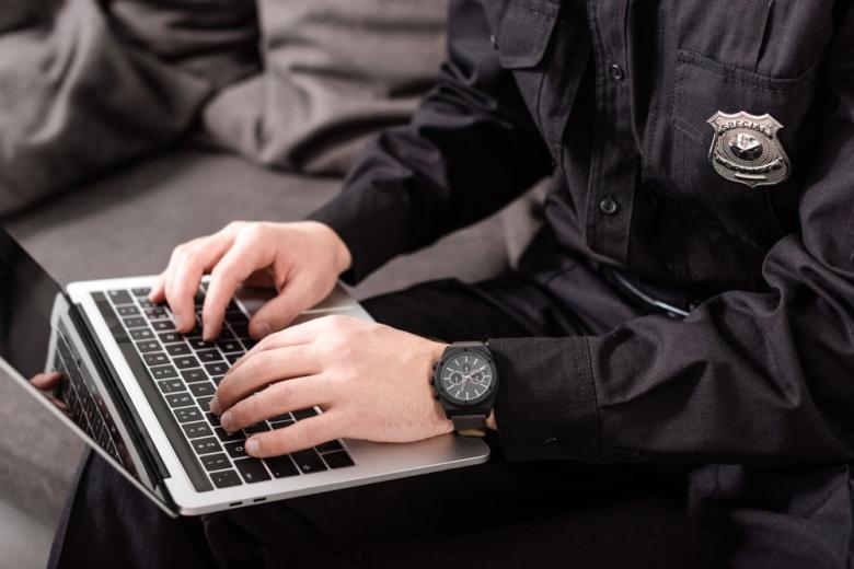 policeman typing on laptop keyboard