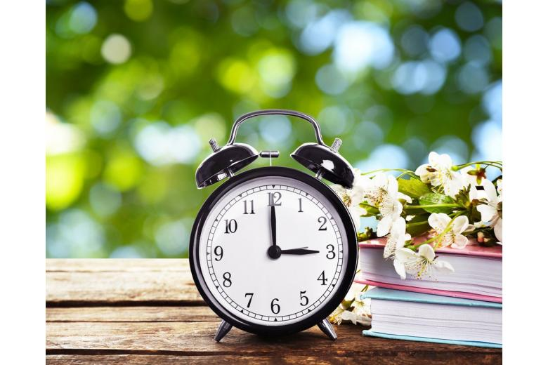 Alarm clock, spring flowers and books