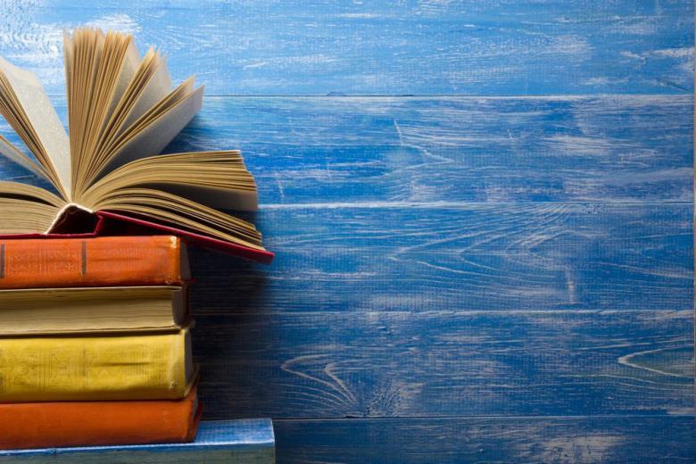 Стопка учебников на деревянном фоне фото