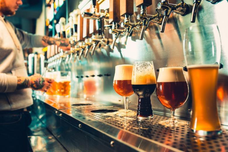 бармен наливает пиво разных видов из крана фото