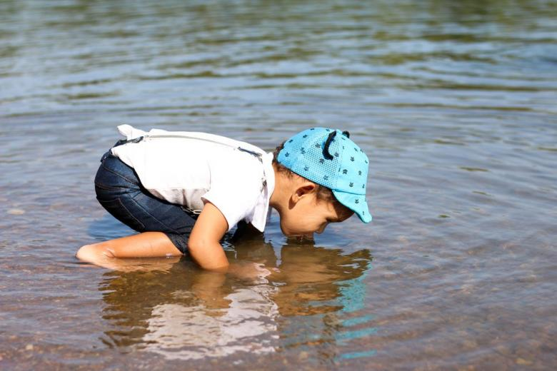 Little boy drinking water from the river