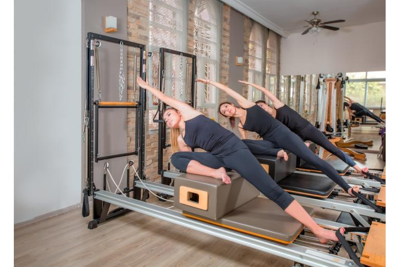 Young women exercising on pilates reformers beds