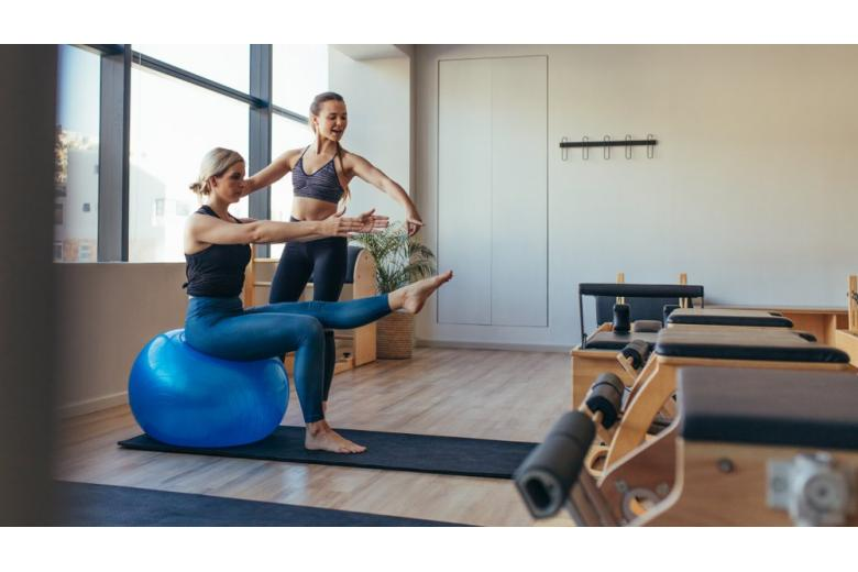 woman doing pilates workout on an exercise ball