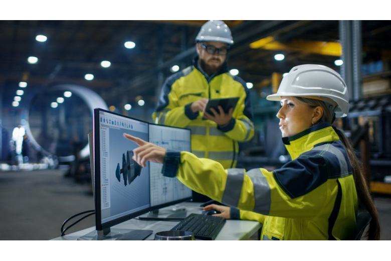Женщина-инжинер с коллегой на предприятии