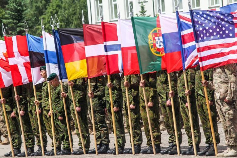 Солдаты держат флаги стран НАТО