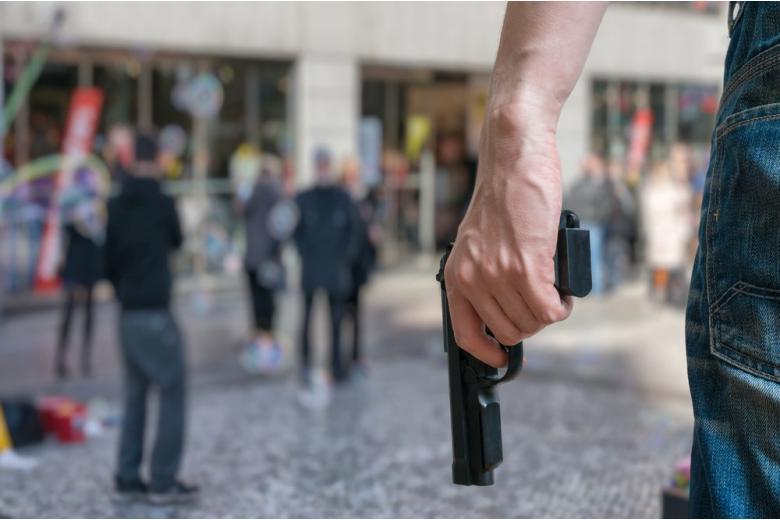 Преступник держиит пистолет на улице