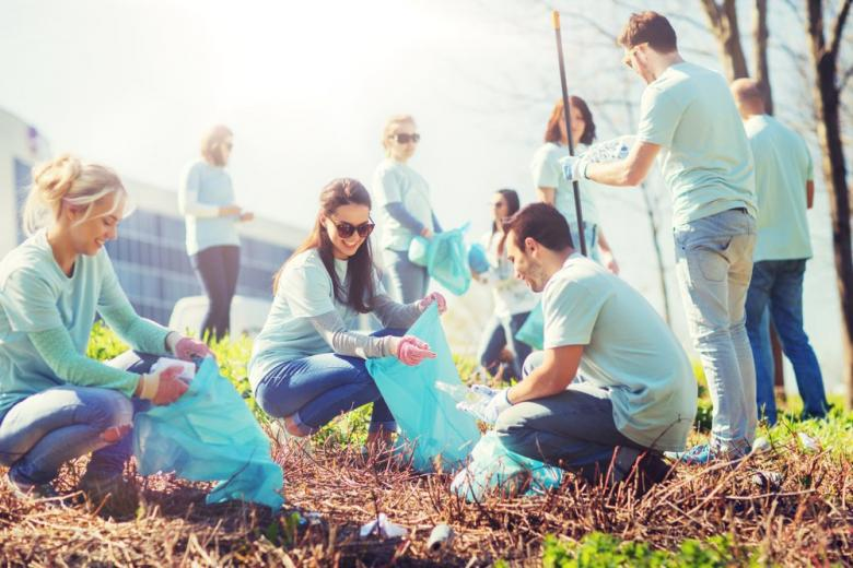 group of happy volunteers cleaning area in park