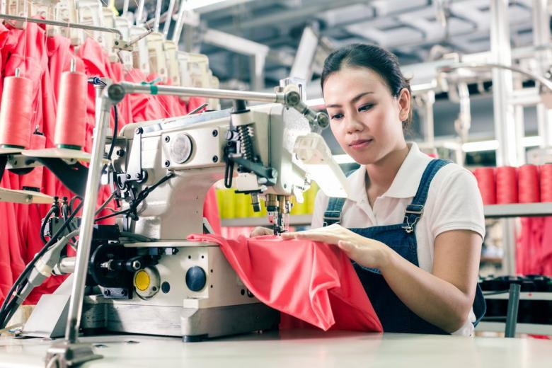 Сотрудница фабрики шьет одежду