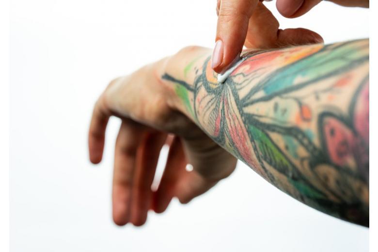 Fingers apply cream to tattoed skin