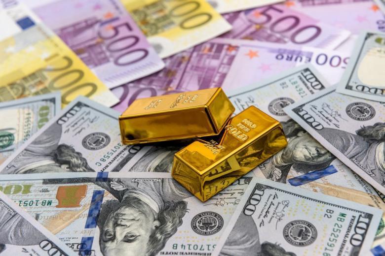Слитки золота и купюры евро