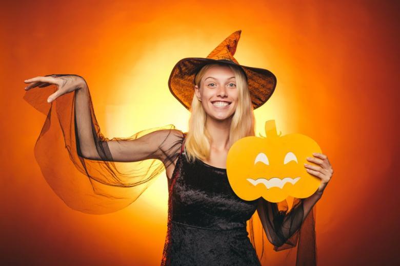 Девушка в костюме ведьмы с тыквой