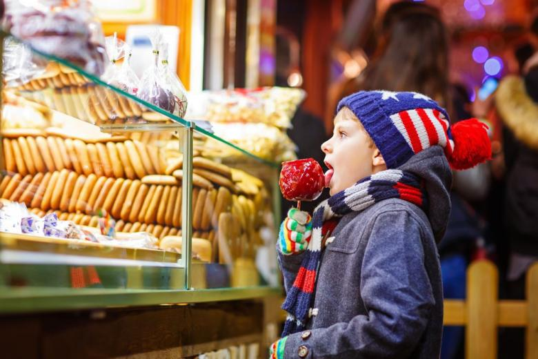 little boy eating sugar apple at the christmas market