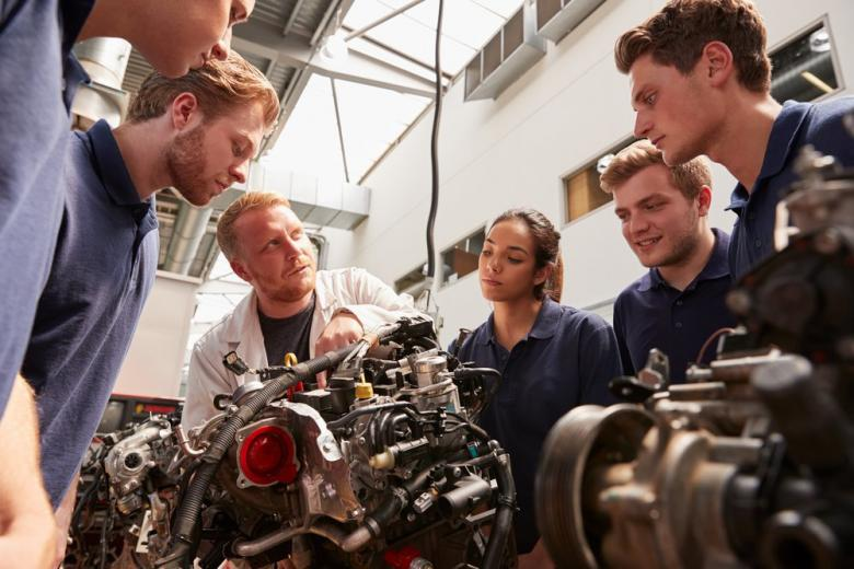 mechanic shows engines to students
