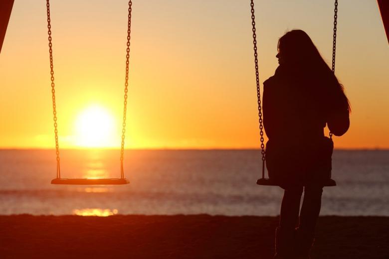 Женщина сама отдыхает на фоне заката