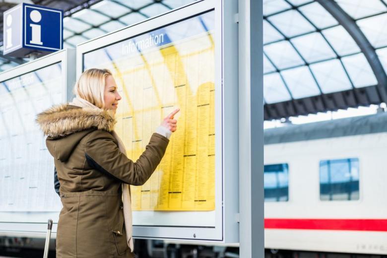 Девушка ищет свой поезд в расписании