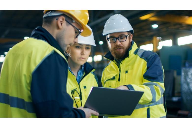 На предприятии стоят в кругу инженеры и рабочие
