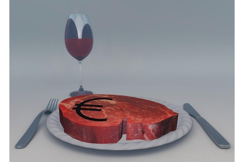 Raw meat with euro sign, glass of wine