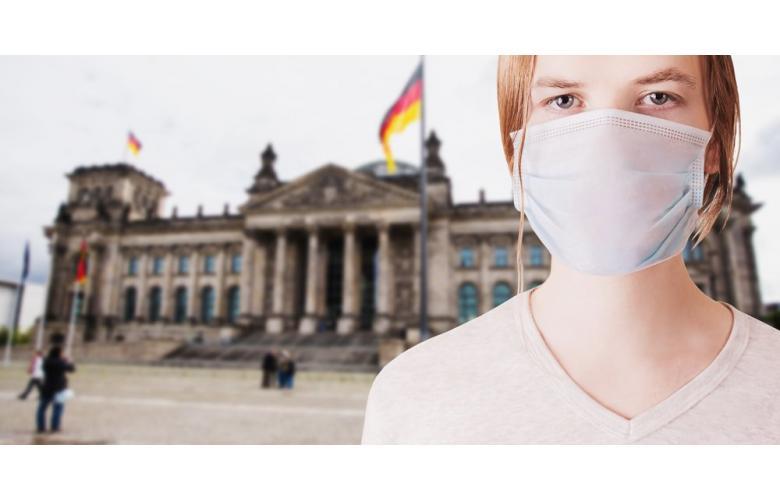 Женщина в маске на фоне Бундестага в Берлине