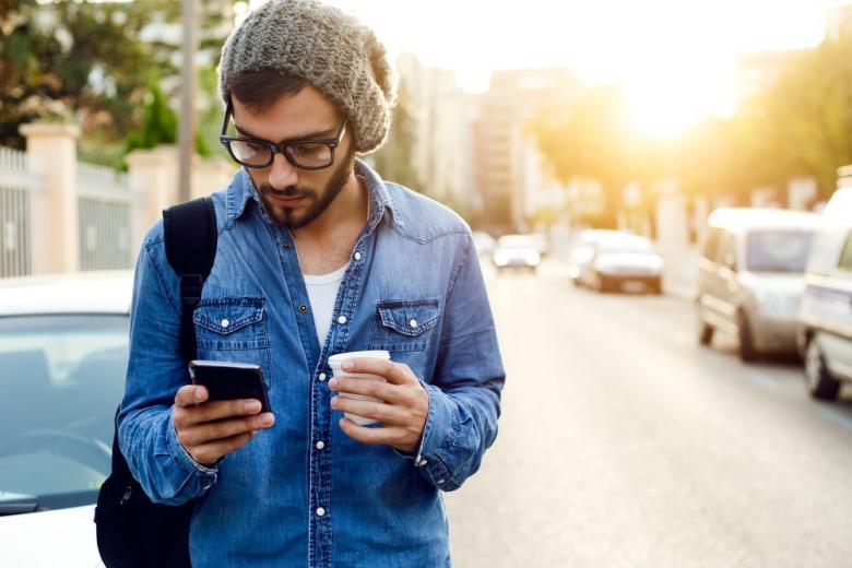 Мужчина пользуется мобильным телефоном
