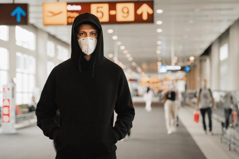 Молодой мужчина в маске соблюдает правила пребывания в аеропорту во время пандемии картинка