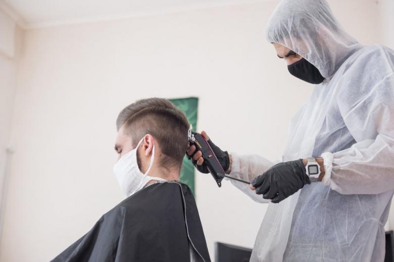 Парикмахер в защитном костюме и маске стрижет клиента фото