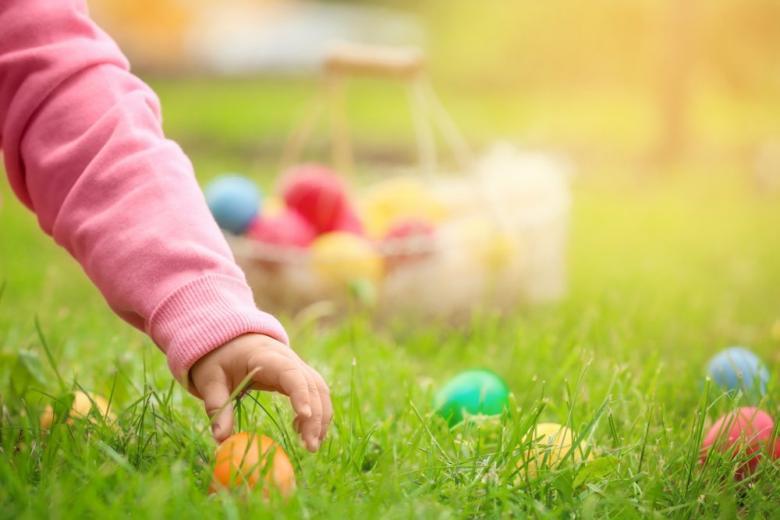 Девочка ищет пасхальные яйца в саду