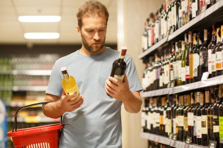 Мужчина покупает вино