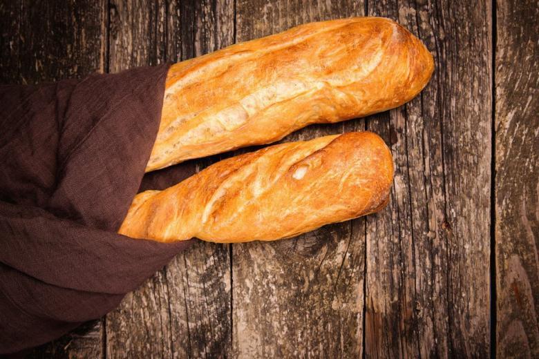Французские багеты в мешке на столе фото