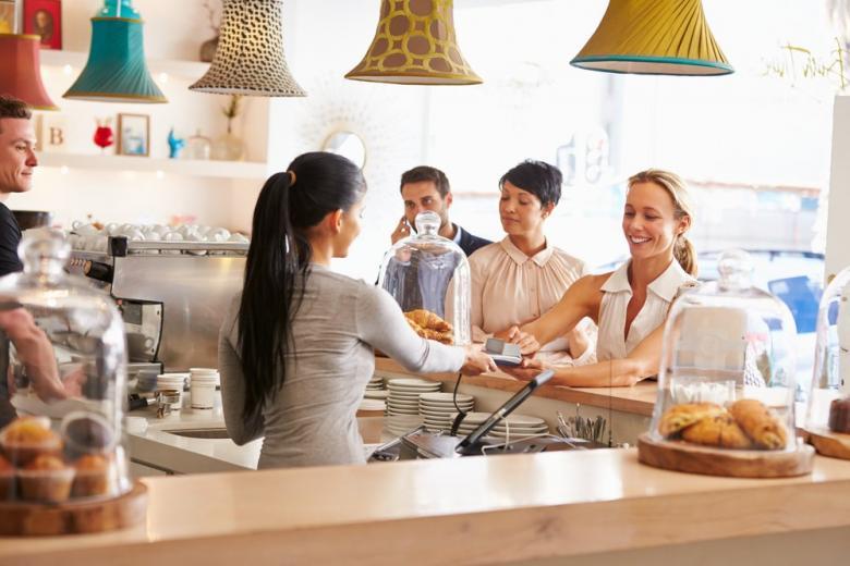 Девушка-студентка работает за стойкой в кафе фото
