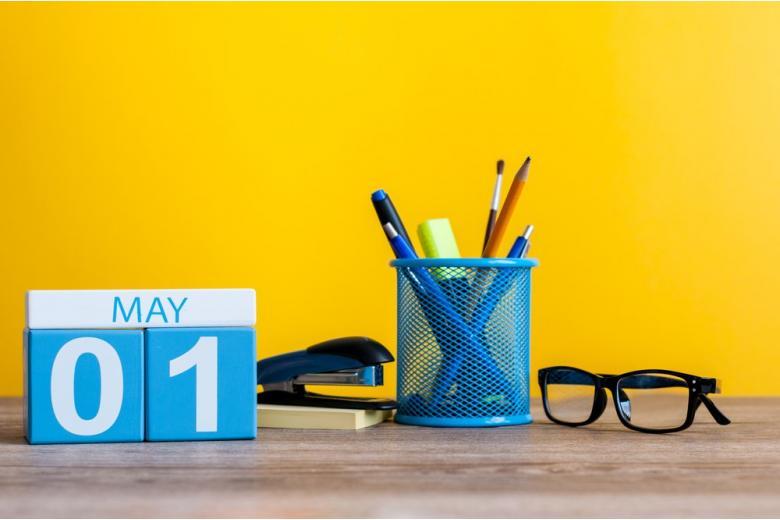 Календарь на май в офисе на желтом фоне фото