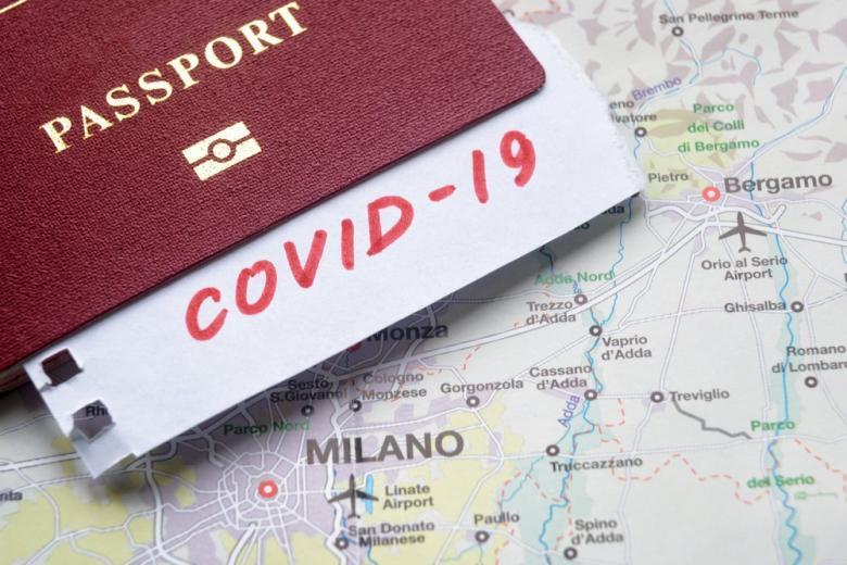 Паспорт на фоне карты Италии с надписью COVID-19 фото
