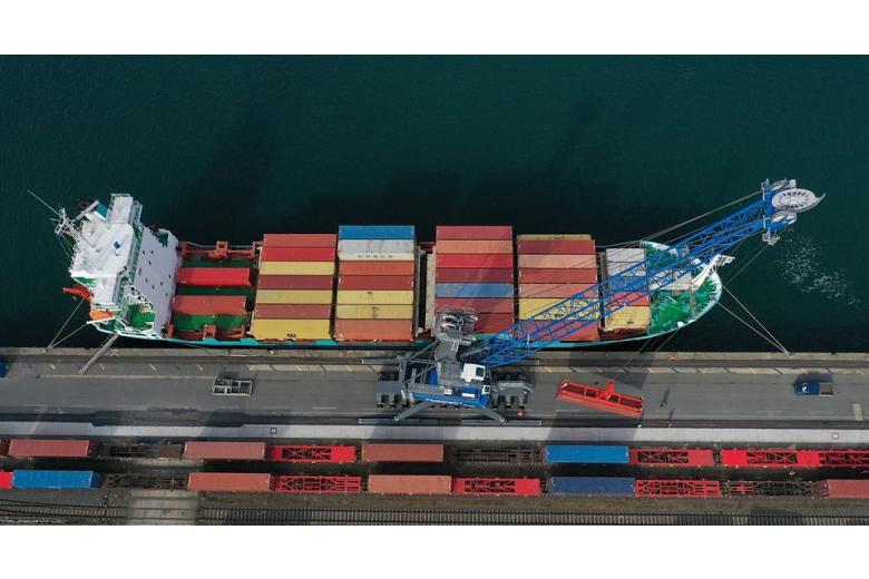 Кран разгружает контейнеры с масками для немецких больниц фото