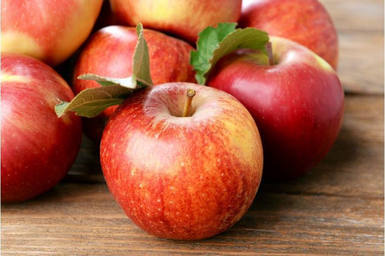 Красные яблоки на деревянном столе фото
