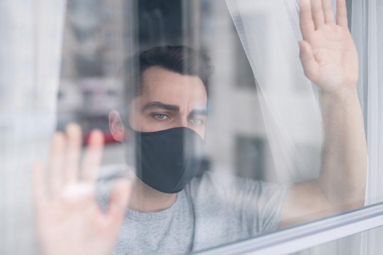 мужчина в маске возле окна