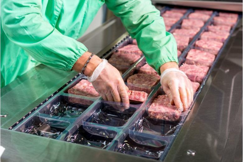 Сотудник мясной фабрики фасует фарш фото