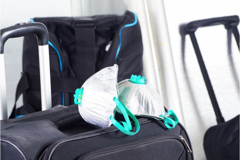 Респираторы на чемоданах, концепт влияния коронавируса на туризм фото